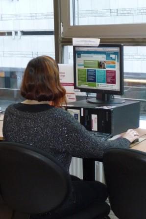Une personne à un ordinateur du Point Emploi