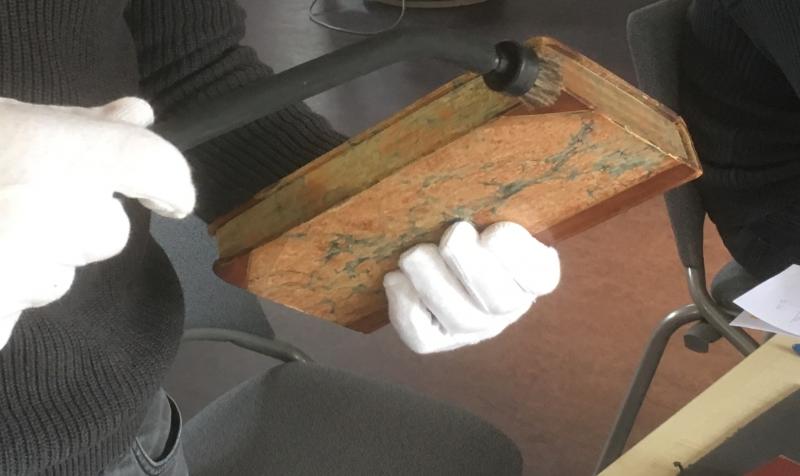 Micro-aspiration de la « gouttière » du livre. La poussière assombri les surfaces et est susceptible de nourrir le microorganisme (tel que la moisissure). Le dépoussiérage est donc un acte de conservation préventif.
