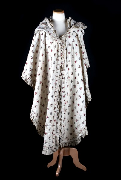 Mantelet de dame en coton imprimé, entièrement bordé d'un volant plissé et garni d'un vaste capuchon froncé à l'arrière de la tête, vu de face, fin du 18e siècle